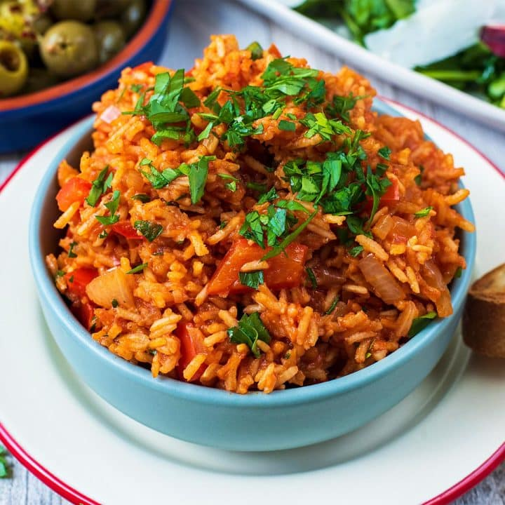 Spanish Rice in a blue bowl topped with chopped parsley