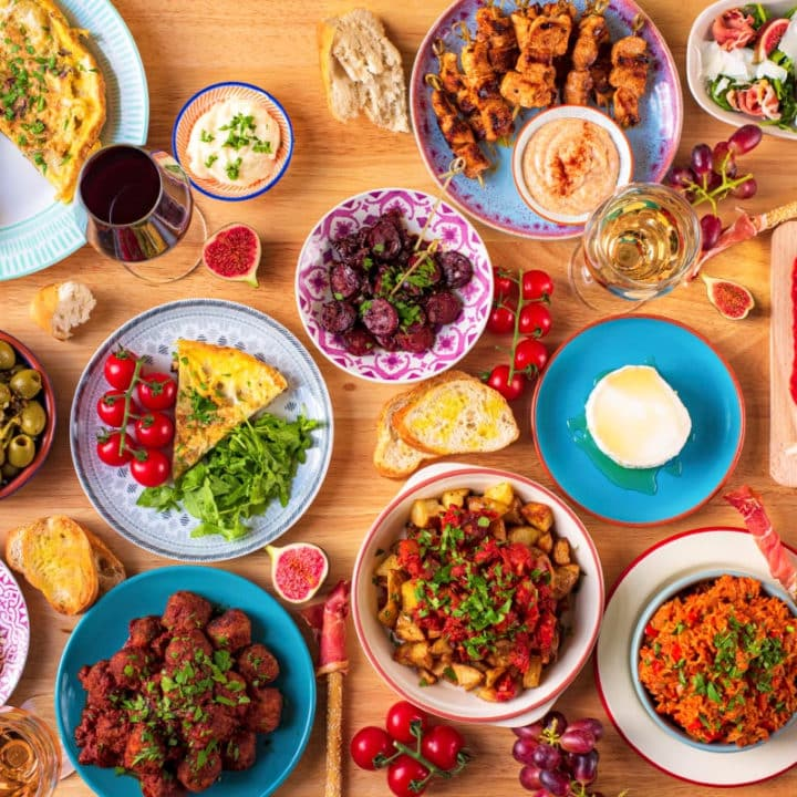 A selection of tapas dishes spread out over a large wooden table
