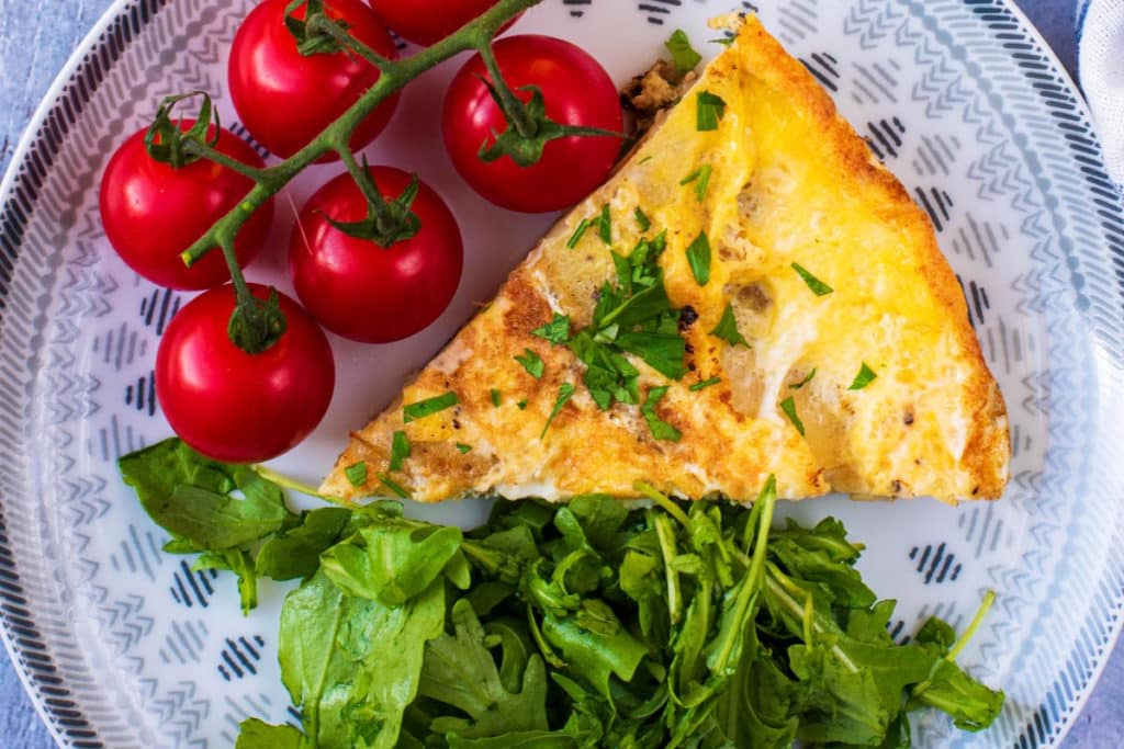 A slice of spanish omelette tortilla with salad and cherry tomatoes