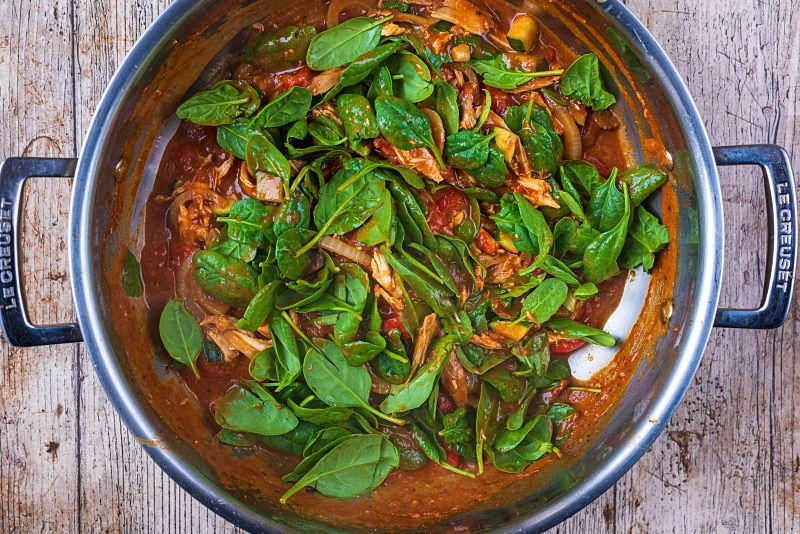 Turkey curry cooking in a large pan with spinach leaves added to it