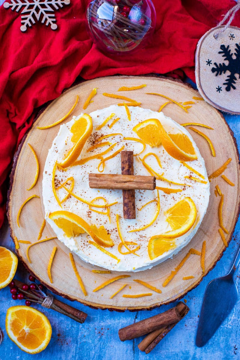 A christmas cheesecake on a wooden board topped with cinnamon sticks and orange slices