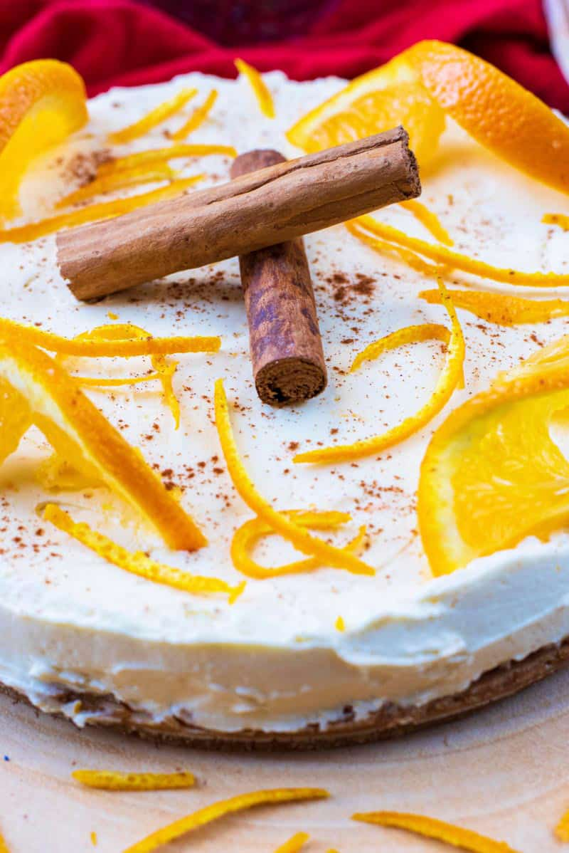 a cheesecake with orange slices, orange peel and two cinnamon sticks on top
