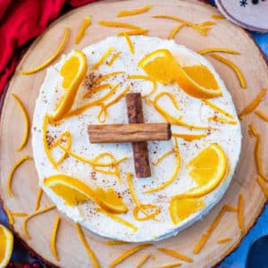 Christmas cheesecake on a borad topped with oranges and cinnamon