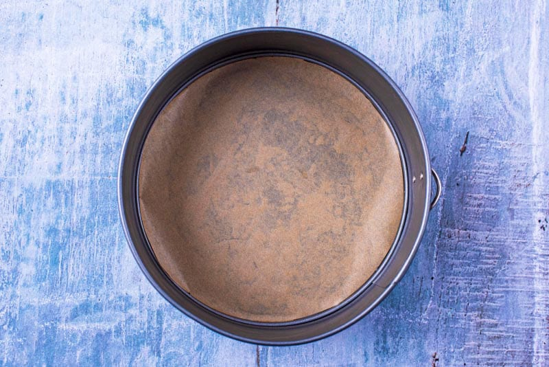 a cake tin with baking paper at the bottom