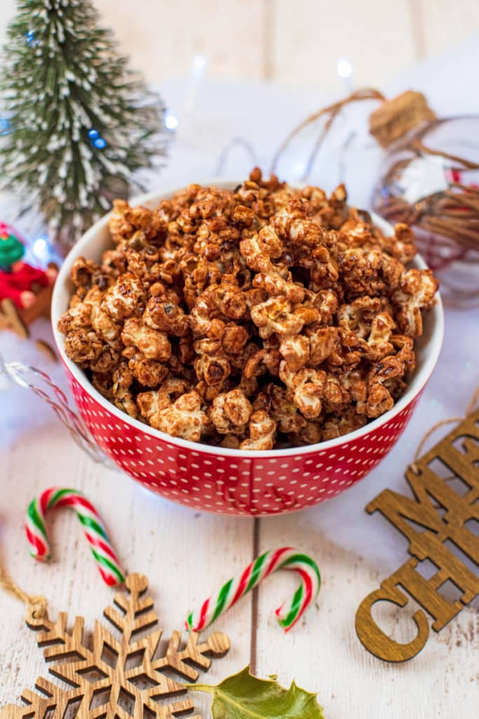 Christmas Popcorn in a red bowl next to Christmas decorations