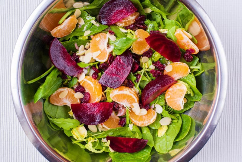 A large metal bowl containing salad leaves, clementine segments and beetroot chunks