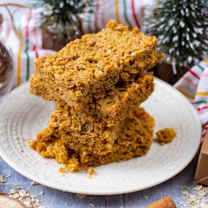 Four cinnamon flapjacks piled on a plate with Christmas decorations in the background