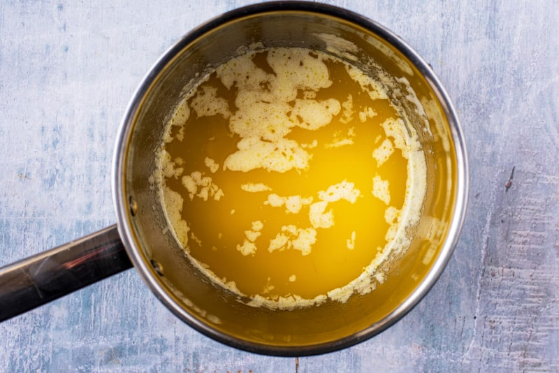 a stainless steel saucepan containing melted butter