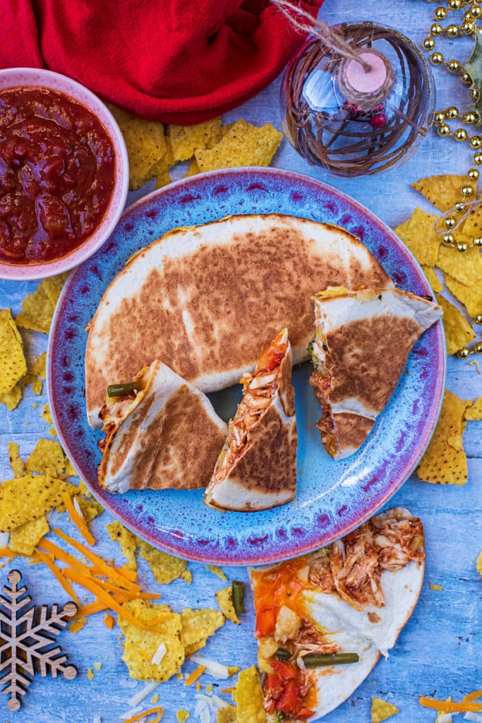 Leftover BBQ Turkey Quesadilla on a blue plate next to a bowl of salsa