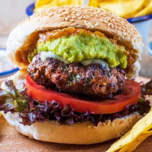 A sesame seed bun containing a Mexican burger, lettuce, tomato, guacamole and relish