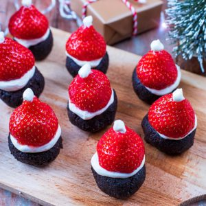 A wooden serving board with nine Santa Hat Brownies