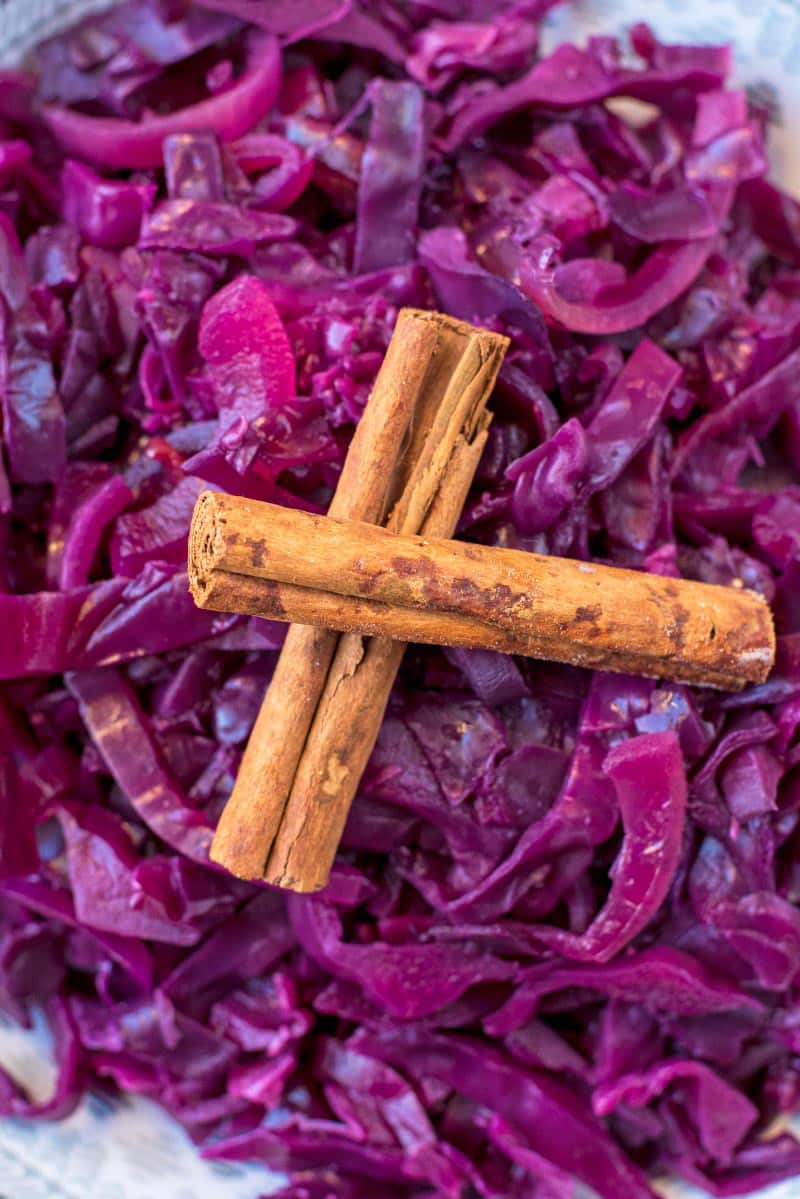 Two cinnamon sticks on top of a big bowl of braised red cabbage