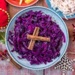 A bowl of slow cooker red cabbage topped with two crossed cinnamon sticks