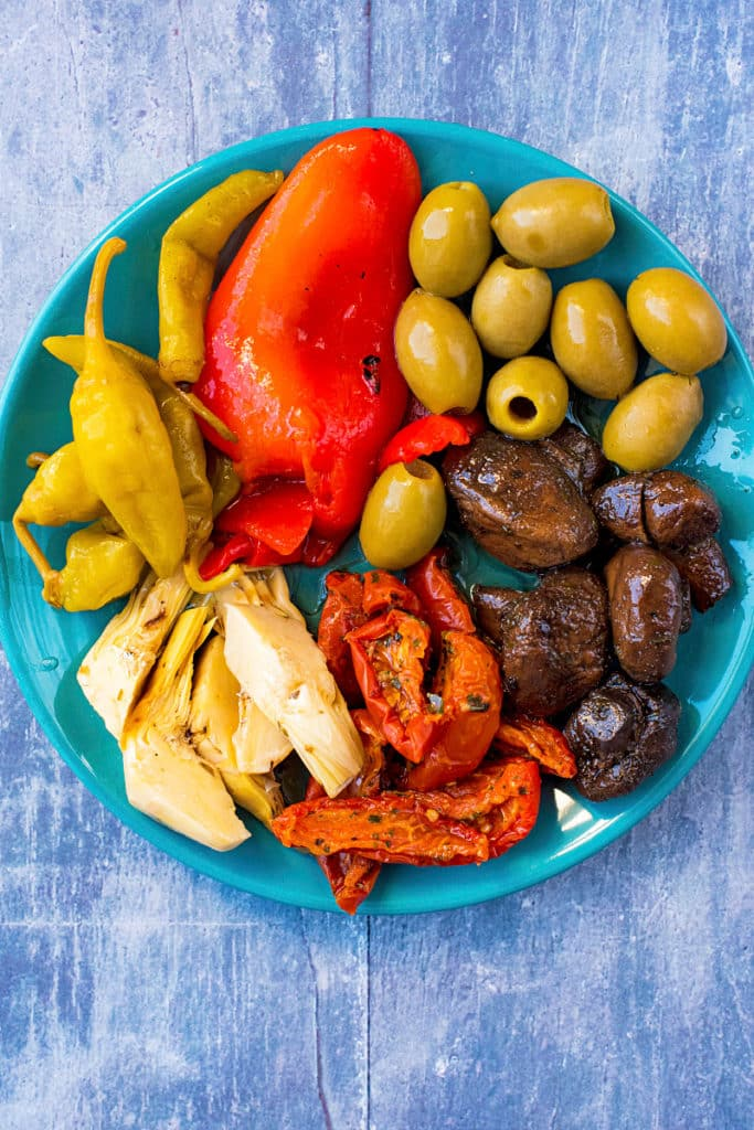 Olives, peppers, mushrooms, artichokes and chillis arranged on a blue plate