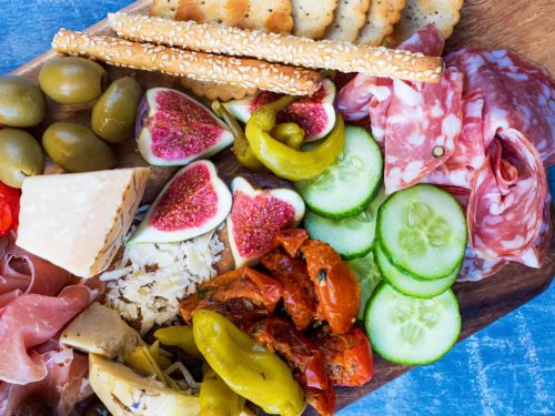 An antipasto platter containing fruit, vegetables, cheese and meats