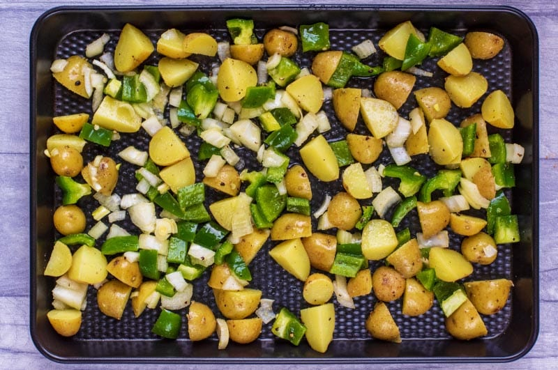 A baking tray covered in cubed potaotes, chopped onions and green bell pepper