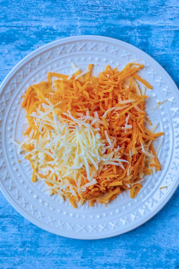 A white plate with a selection of grated cheese
