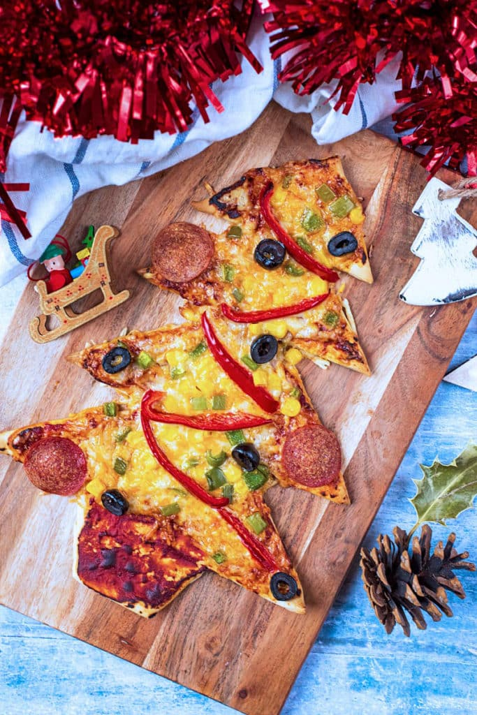 A Christmas Tree Pizza on a wooden board with red tinsel next to it