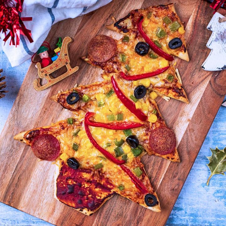 A Christmas Tree Pizza on a wooden board with Christmas decorations surrounding it