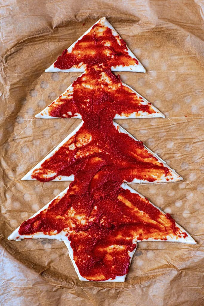 Pizza dough cut into a tree shape covered in tomato sauce