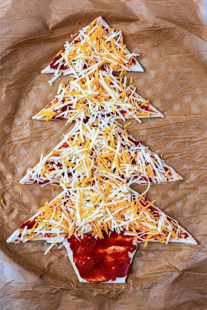 Pizza dough cut into a tree shape covered in tomato sauce and grated cheese