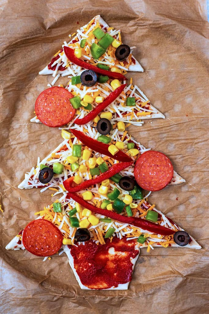 Pizza dough cut into a tree shape covered in tomato sauce, grated cheese, vegetables and salami