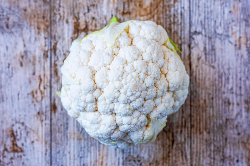 A large head of cauliflower on a wooden surface