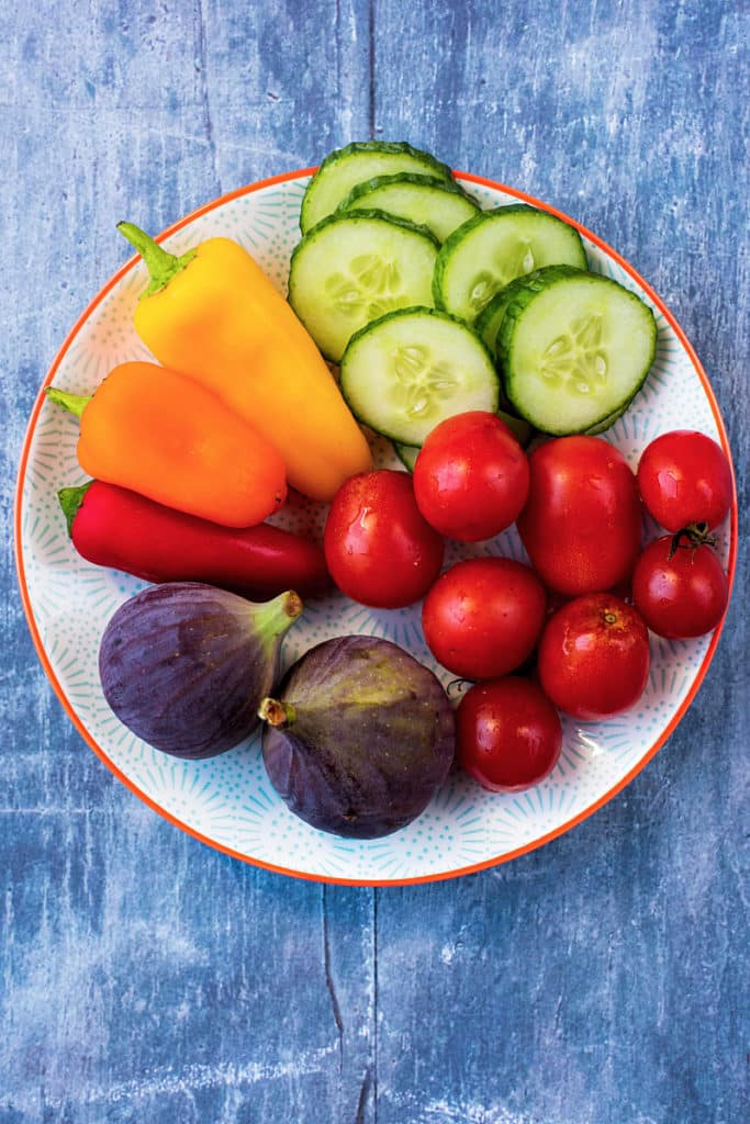 Sliced cucumber, cherry tomatoes, sweet peppers and figs on a white plate