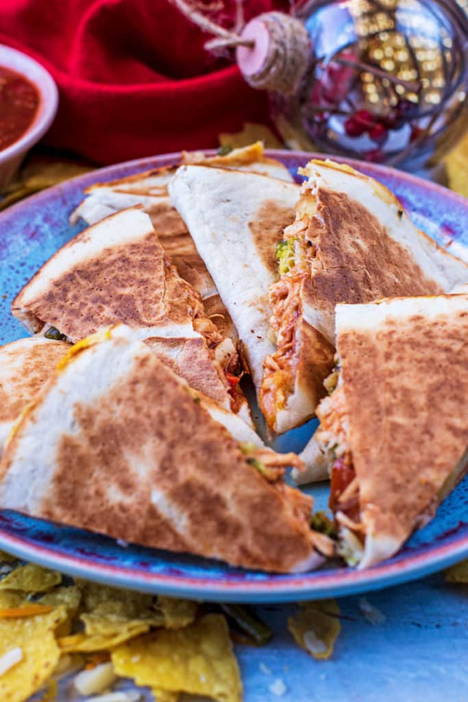 Sliced up turkey quesadillas in front of some Christmas decorations