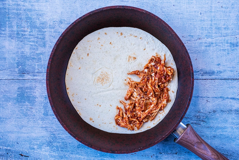 A flour tortilla in a frying pan with barbecue chicken on half of it