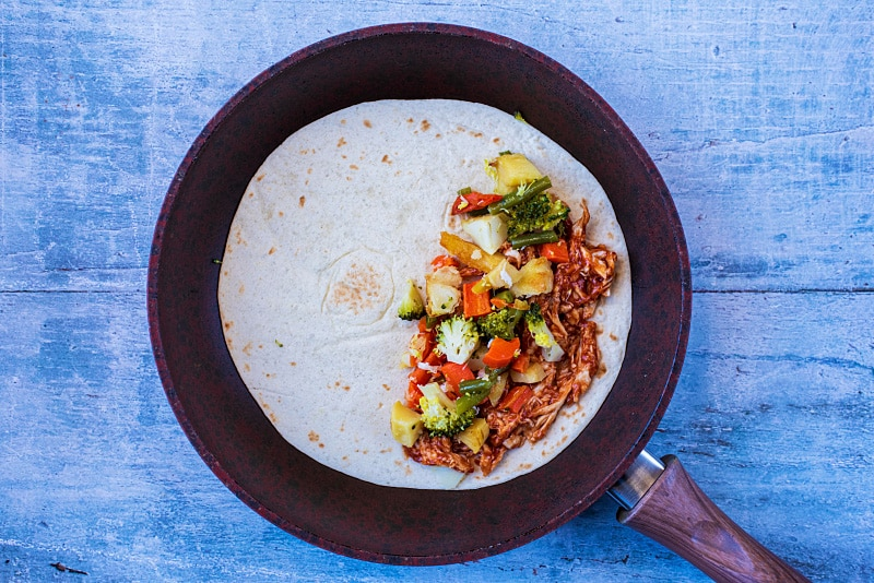 A flour tortilla in a frying pan with barbecue chicken and chopped vegetables on half of it