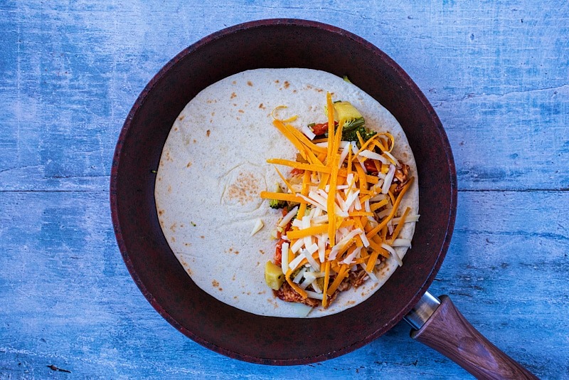 A flour tortilla in a frying pan with barbecue chicken, chopped vegetables and grated cheese on half of it