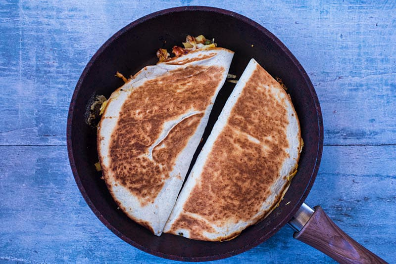 a frying pan with two cooked quesadillas
