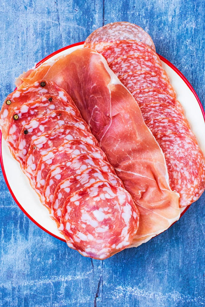 A selection of three cured meats on a white plate