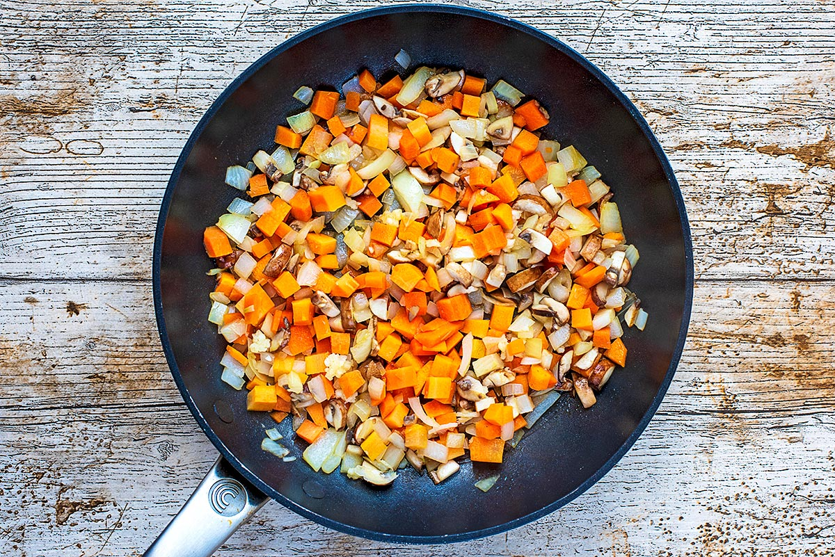 A frying pan with chopped carrot, onion, mushrooms and garlic