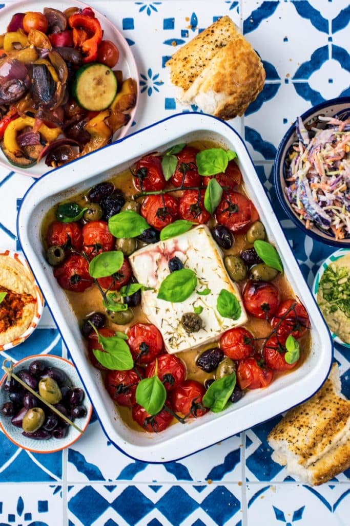 Baked Feta in a rectangular baking dish with cherry tomatoes, olives and basil leaves