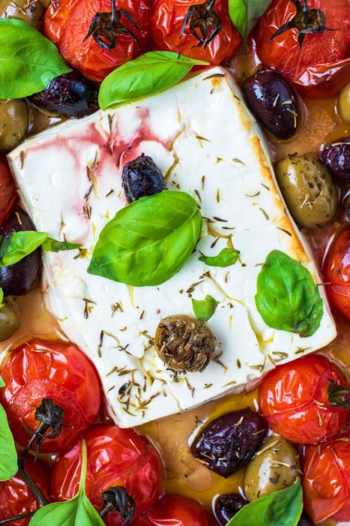 A block of baked feta cheese surrounded by roasted cherry tomatoes