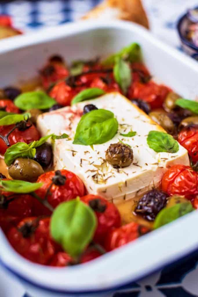 Feta cheese, tomatoes, olices and basil in a white baking tray