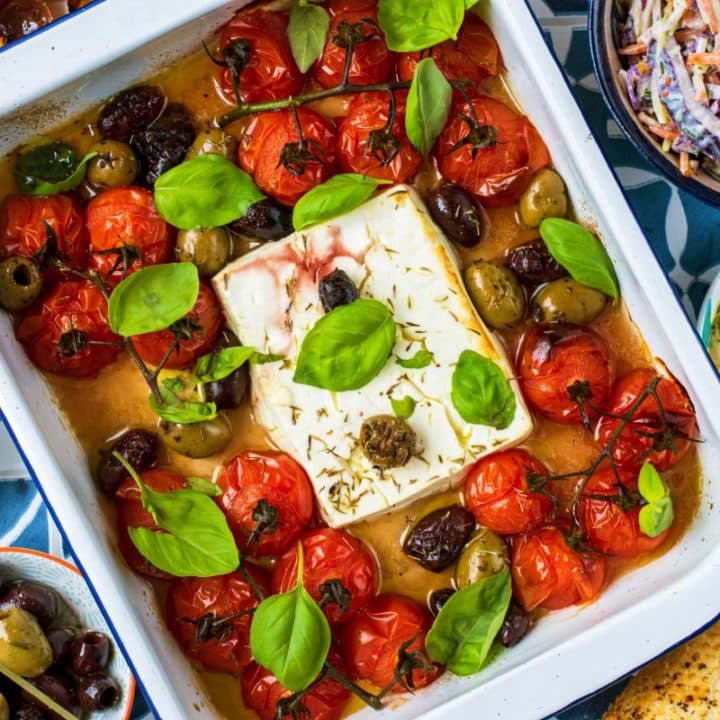 Baked Feta with tomatoes in a white baking dish. Olives, hummus, slaw and bread surround it