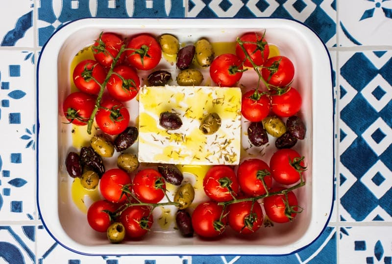 A whole block of feta surrounded by tomatoes and olives all in a baking dish. Olive oil has been drizzled over everything