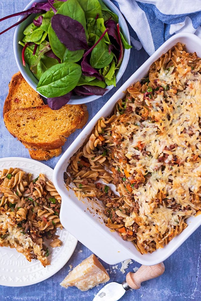 Bolognese pasta bake in a white baking dish next to a bowl of salad and some garlic bread
