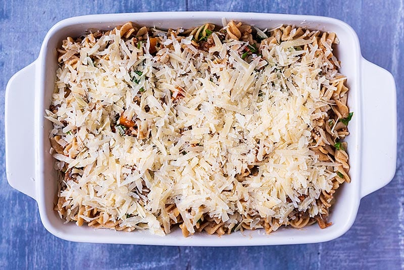 Pasat bolognese in a baking dish covered in grated cheese