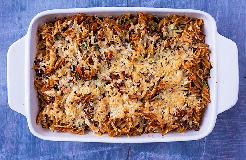 Bolognese pasta bake in a baking dish covered in melted cheese