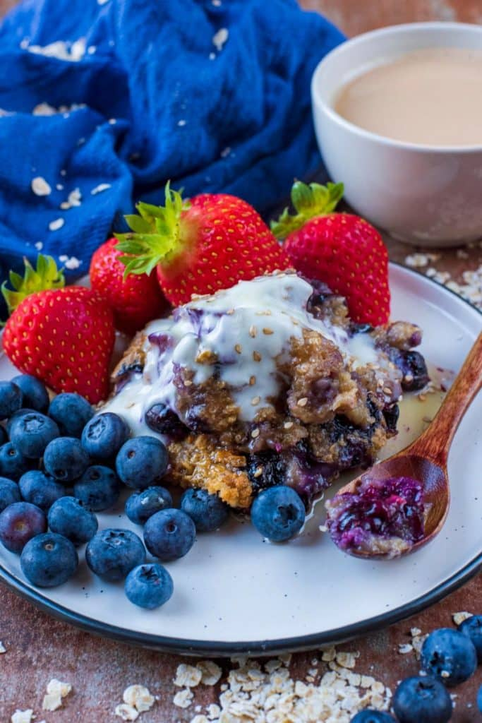 Baked oats, berries and a small spoon on a white plate