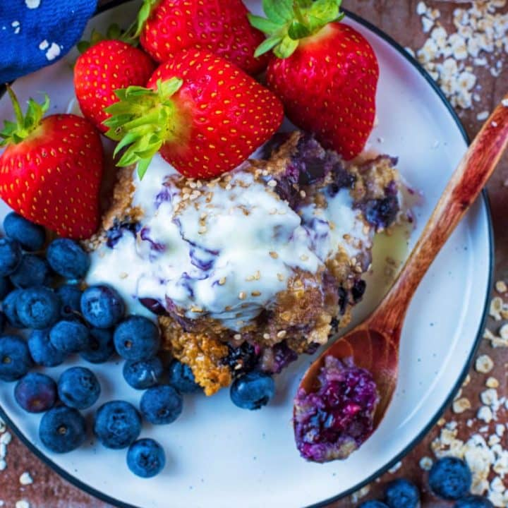 Easy Baked Oats on a white plate with fruit and a spoon