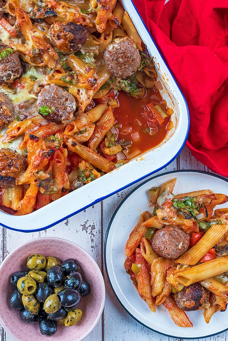 Meatball pasta bake in a large baking dish and on a white plate. A small bowl of olives is next to them