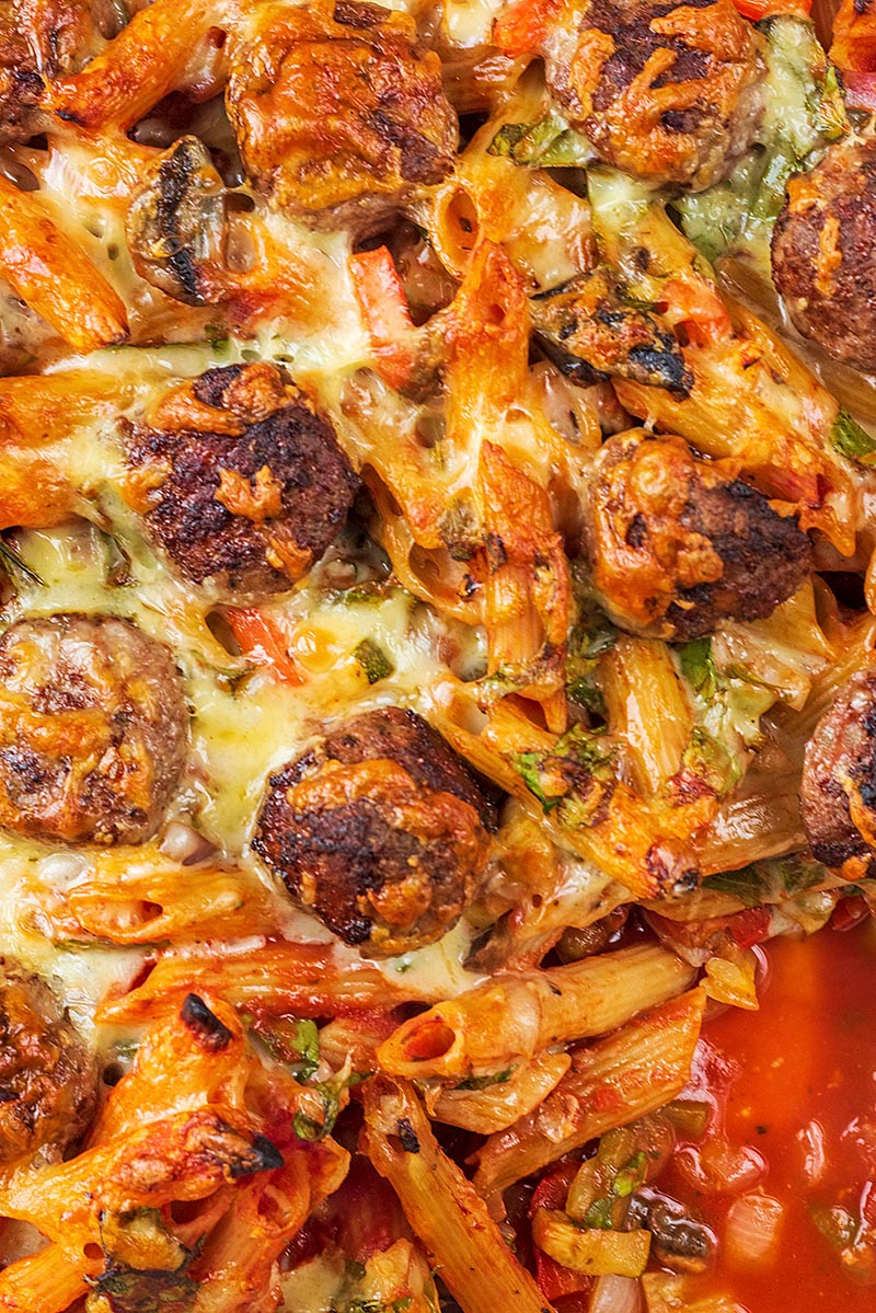 Meatballs and penne pasta in a tomato sauce covered in melted cheese