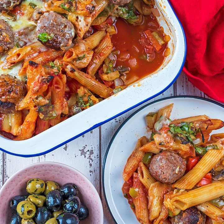 A tray of meatball pasta bake next to a plate of some more pasta bake
