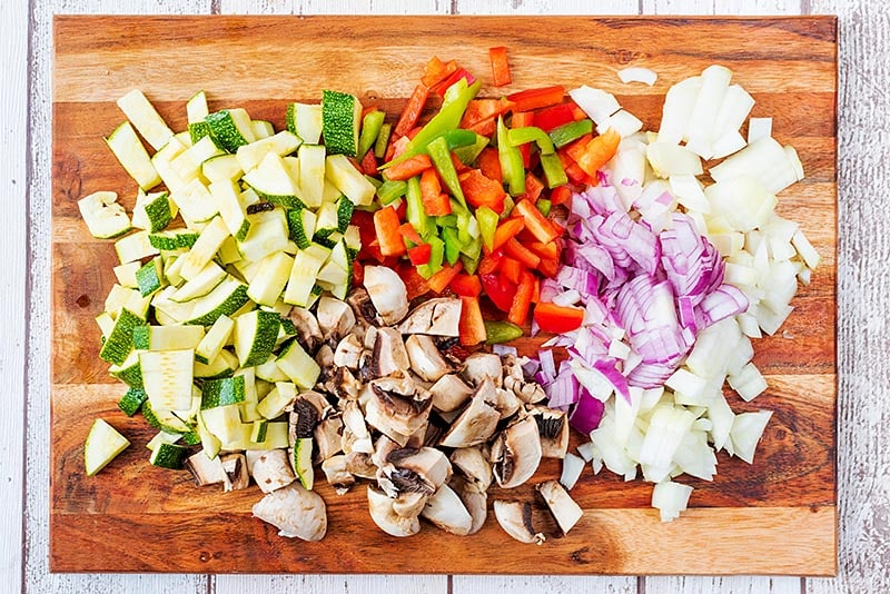 A wooden chopping board covered with chopped vegetables