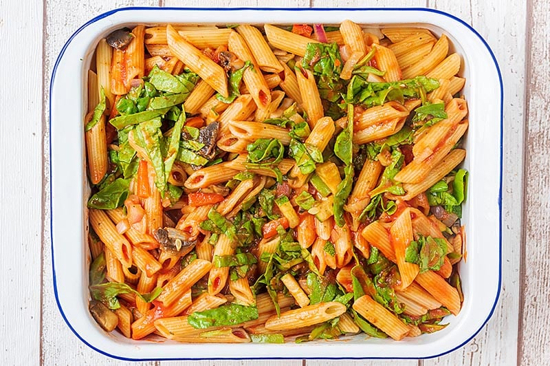 A large rectangular baking dish containing cooked pasta and chopped vegetables all in a tomato sauce